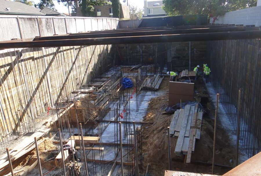 Form work and vertical ironwork for a poured in place retaining wall and basement. Pacificland Constructors