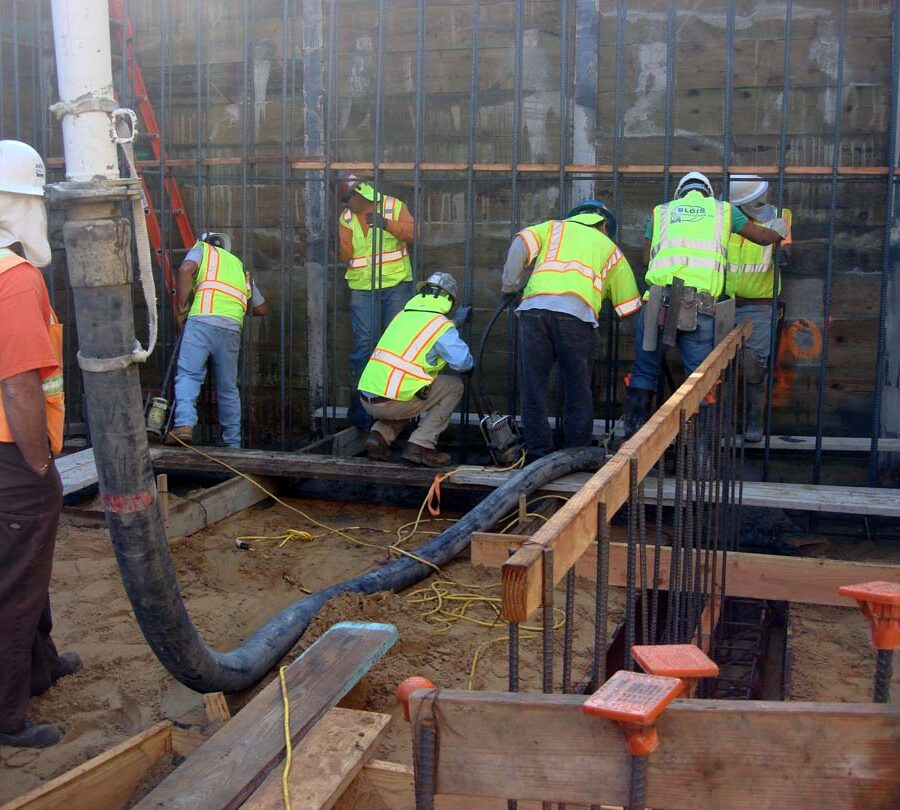 Pouring concrete into the strip footings of retaining walls. Pacificland Constructors