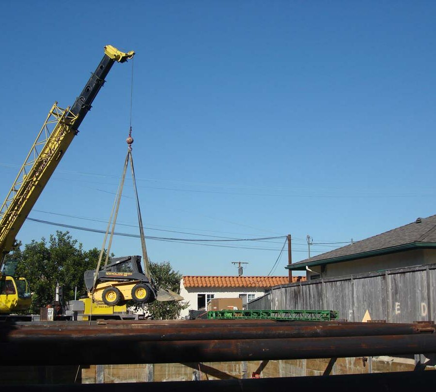 Use of a hydraulic crane to haul in a mini bobcat and steel rebar. Pacificland Constructors