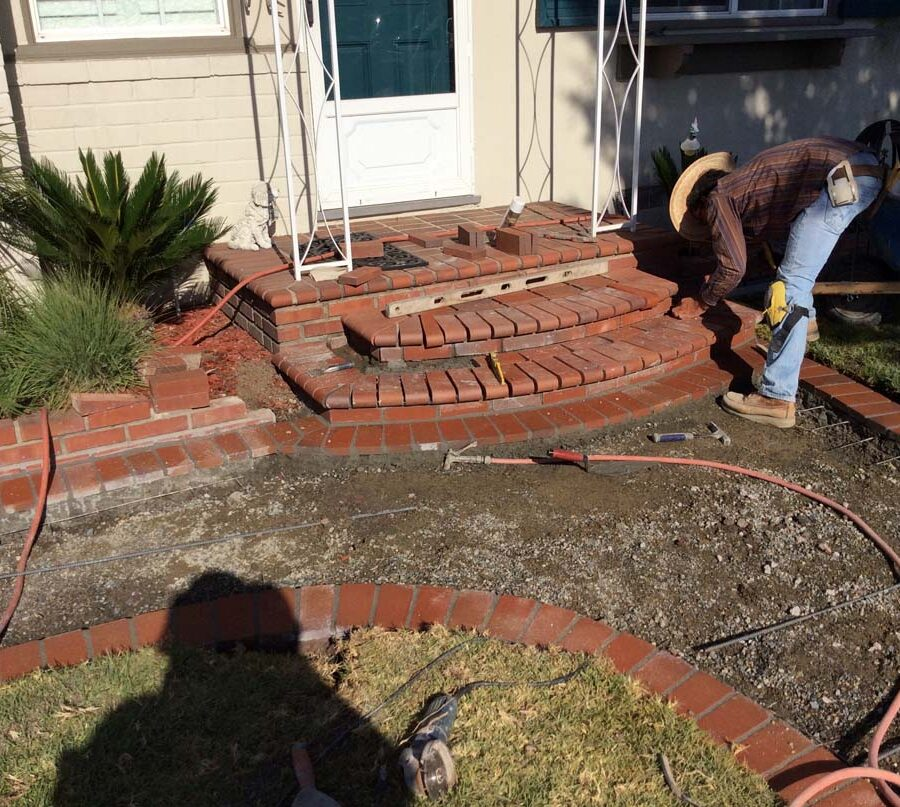 Construction of curved walkway entrance with brick ribbon and a nice brick front porch landing. The reinforced flatwork will be poured with gray concrete. Pacificland Constructors