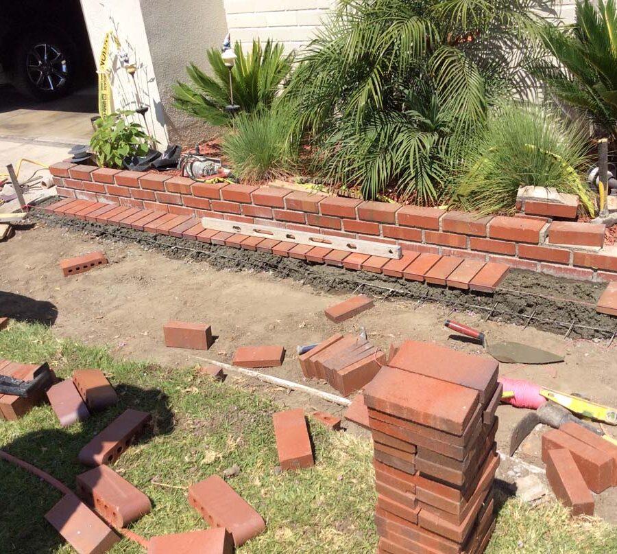 Construction of the new walkway's brick ribbon and brick planter.