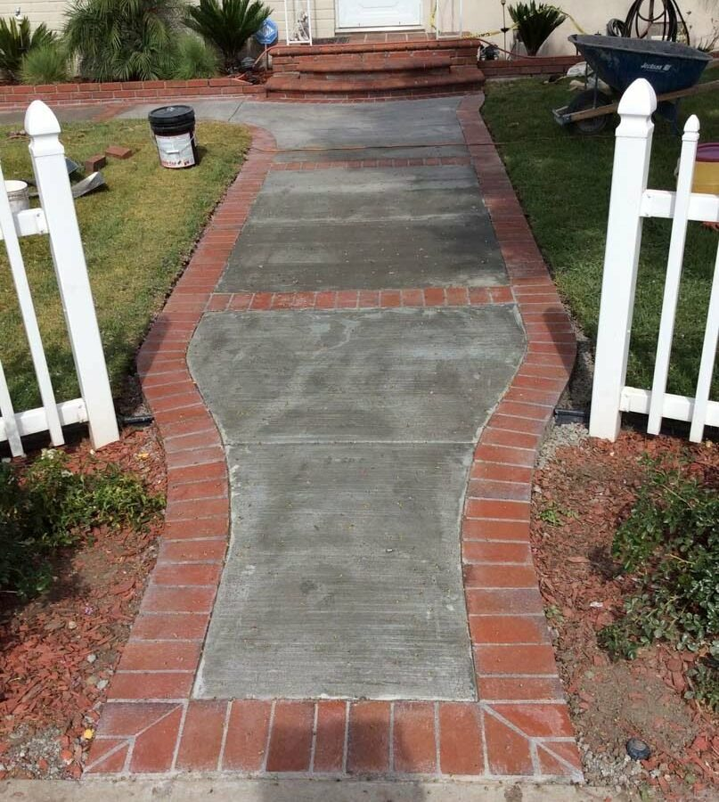 Beautiful curved walkway entrance with brick ribbon and a nice brick front porch landing. Pacificland Constructors