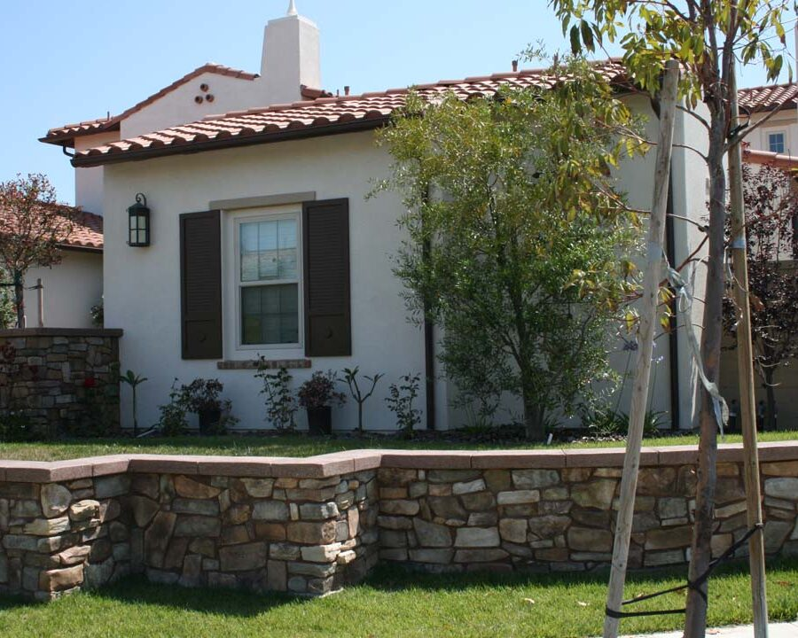 New stone veneer on the main entrance solidifies the Spanish architectural theme of the home. Pacificland Constructors