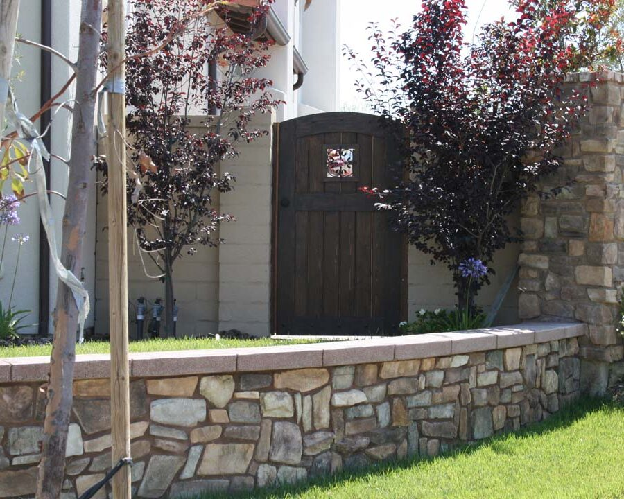 Concrete poured wall cap poured over a stone veneer concealing the CMU planter. Pacificland Constructors