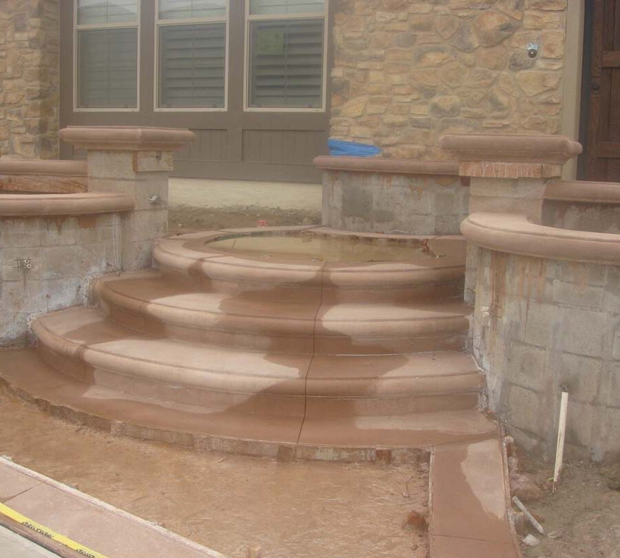 Construction of a new home entrance. New bull-nosed poured steps and CMU planters with poured wall cap prior to putting stone veneer on these planters. It had rained that weekend making a puddle where flagstone flatwork will be. Pacificland Constructors