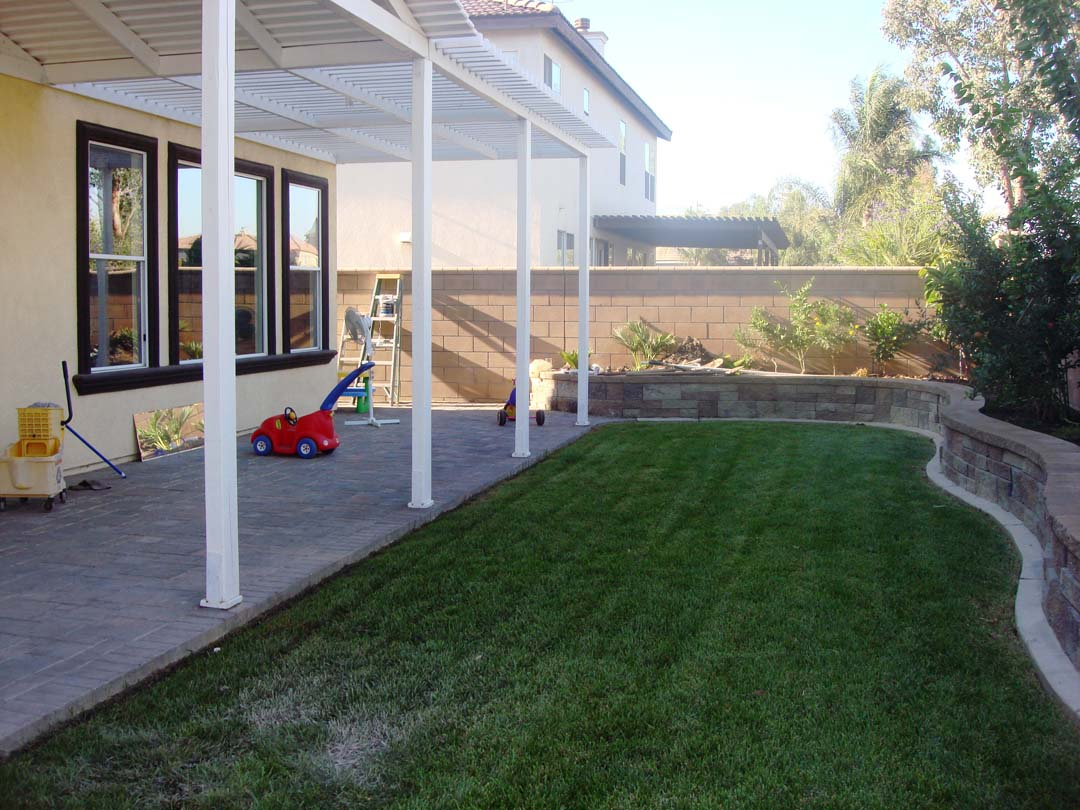 New pavers for the covered patio and stone veneer to conceal CMU planters to give the home an architecturally vintage look. Pacificland Constructors