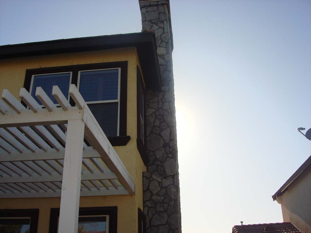 New stone veneer to conceal brick chimney to give the home an architecturally vintage look. Pacificland Constructors