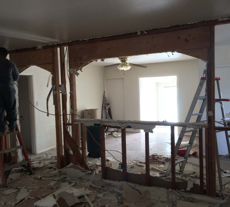 Demolition of existing drywall to expose the load bearing wall.