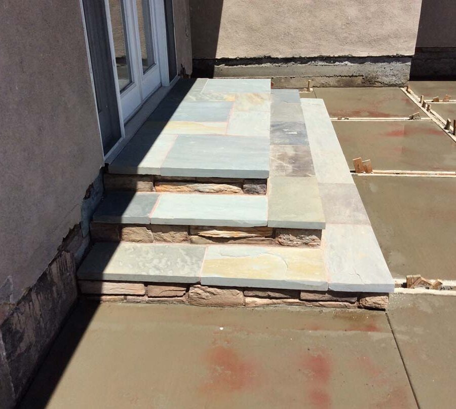 New concrete backyard steps with stone slates and a patio with an architecturally nature-friendly theme. Pacificland Constructors