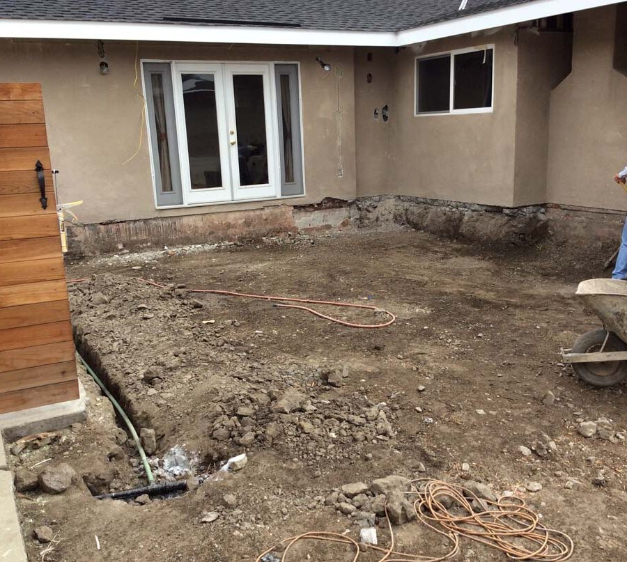 Grading and drainage installation for a new concrete backyard patio with an architecturally nature-friendly theme. Pacificland Constructors