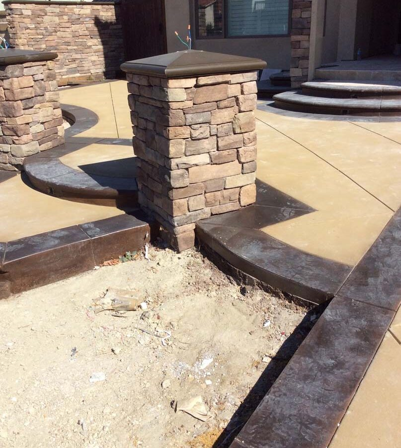 New custom entrance with colored concrete, stone covered pilasters, and concrete poured bull-nosed steps that contrast from the center of the slab. Pacificland Constructors