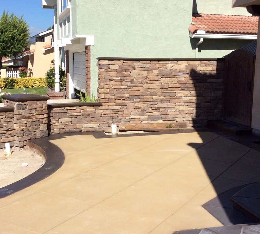 New custom entrance with colored concrete, stone covered pilasters, and concrete poured bull-nosed steps & wall cap that contrast with the light colored slab. Pacificland Constructors