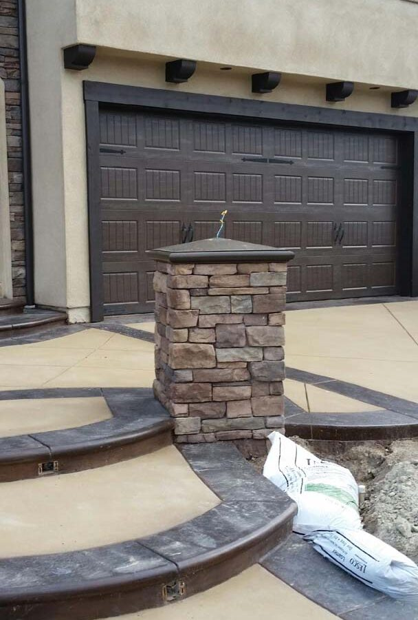 New custom entrance with colored concrete, stone covered pilasters, and concrete poured bull-nosed steps that contrast from the center of the slab.