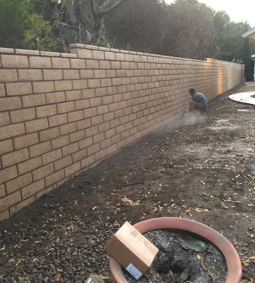 Construction of a new tan colored slump block freestanding wall for a backyard along the centerline of the property lines.