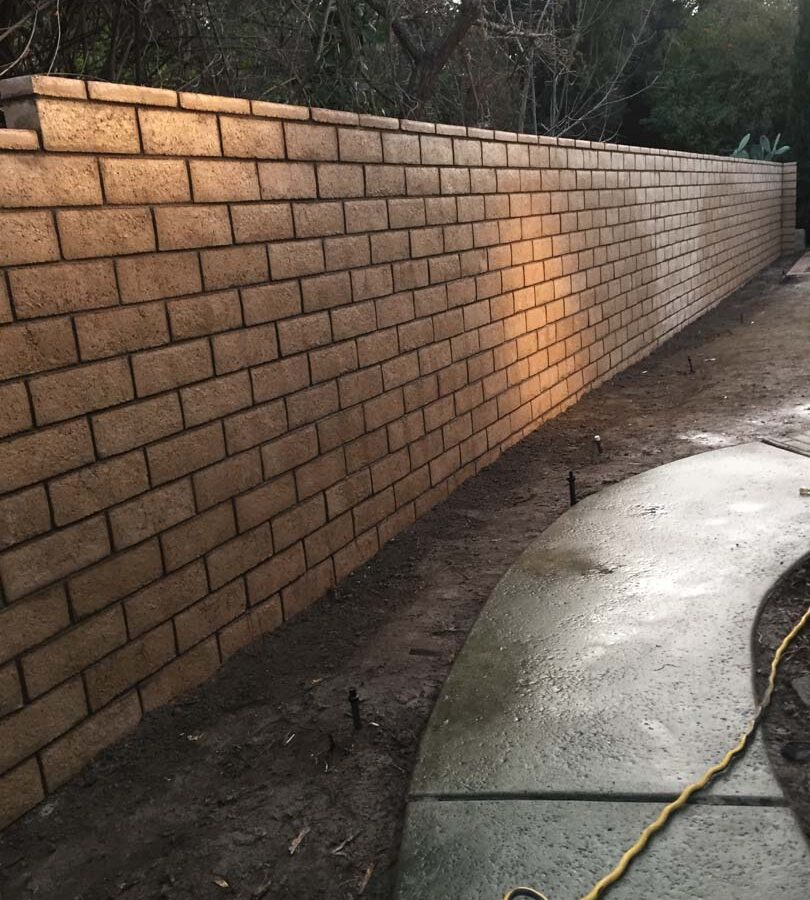 New tan colored slump block freestanding wall for a backyard along the centerline of the property lines.