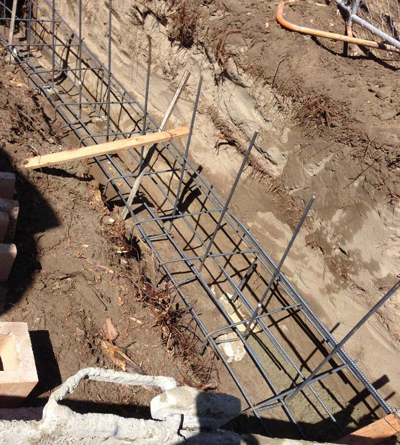 Concrete pouring of strip footings for new public works curved split-faced-block freestanding wall. Pacificland Constructors