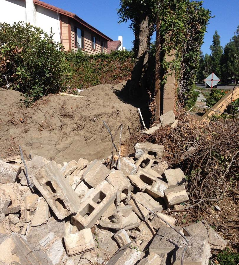 Demolition of the existing freestanding wall that was built without grout. This is an unsafe practice used by unlicensed contractors that steal money from owners by not giving them quality work. Pacificland Constructors