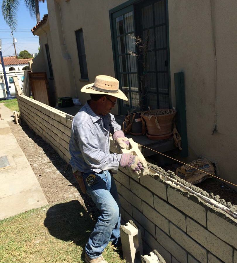 Martin, founder of Pacificland, laying slump block for a home's side yard. This is a great option to raise the value of your home and create more private living space. Pacificland Constructors
