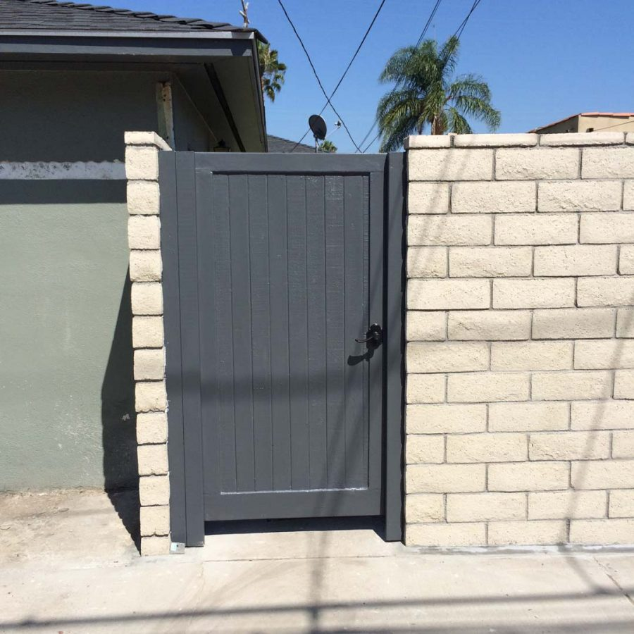 New slump block CMU wall with a wall cap for a home's backyard. This is a great option to raise the value of your home and create more private living space. It also has access to a back alley with this wooden door. Pacificland Constructors