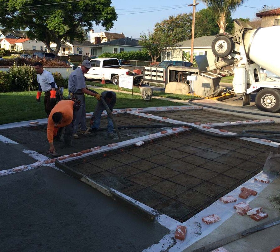 Pouring a new gray concrete driveway with brick ribbons. Pacificland Constructors