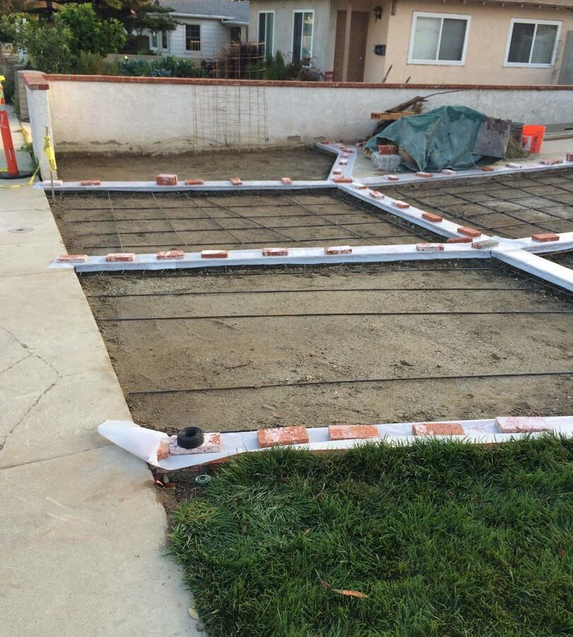 Installing steel reinforcement of a new gray concrete driveway with brick ribbons. Pacificland Constructors