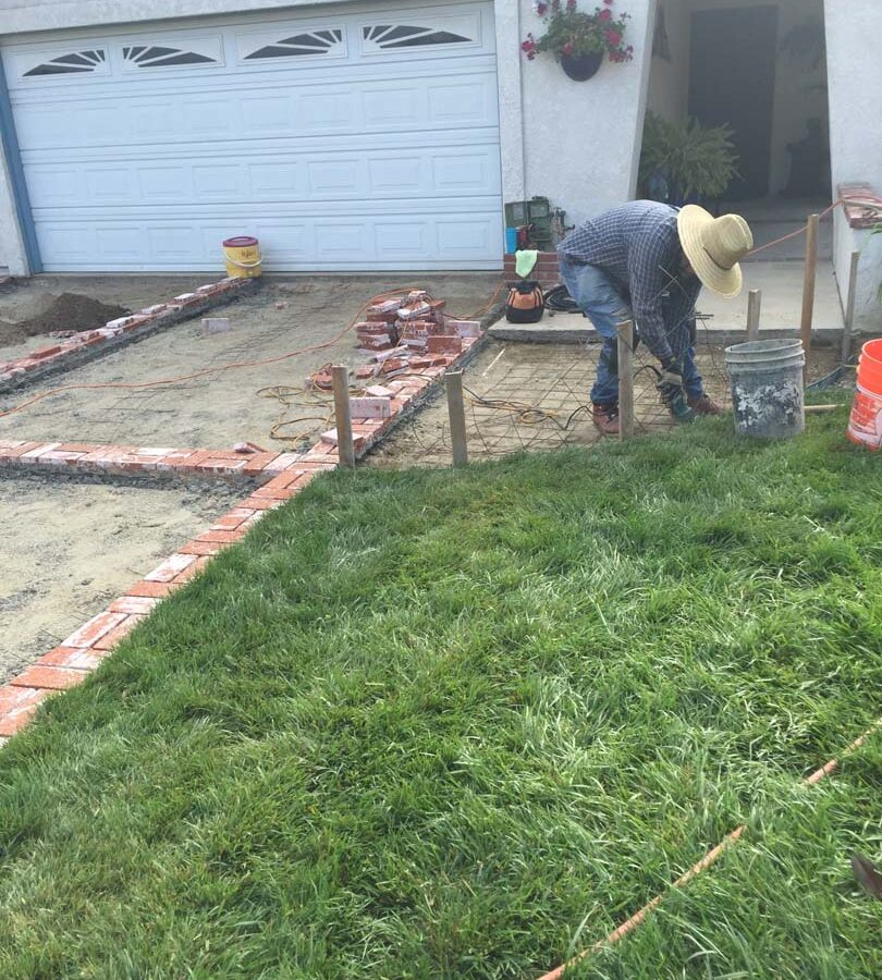 Installing new brick ribbons for a driveway. Pacificland Constructors
