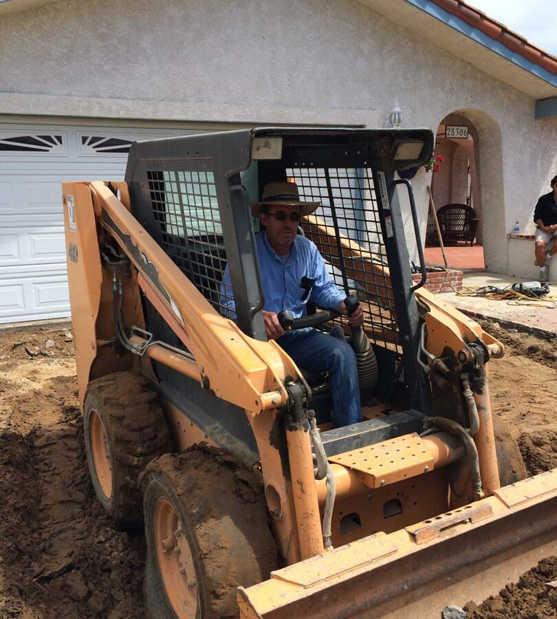 Founder of Pacificland, Martin, using a machine to demolish the outdated driveway.
