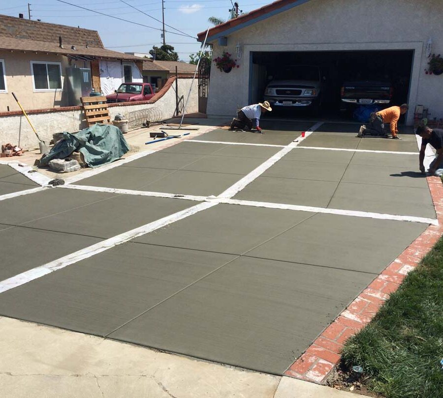 New broom swept gray concrete driveway with brick ribbons. Pacificland Constructors