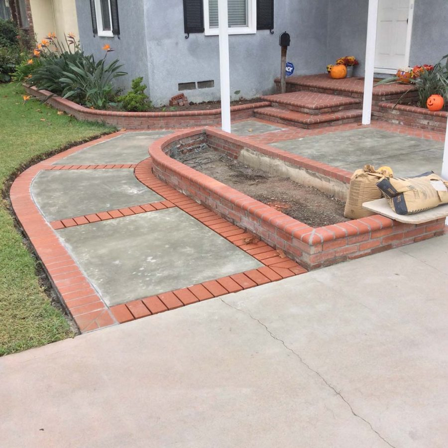 Construction of new concrete slab with brick ribbon and brick planters. Pacificland Constructors