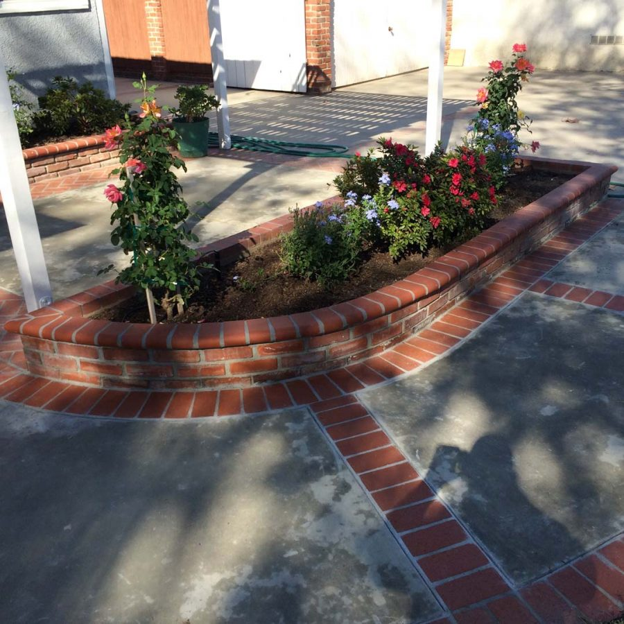New concrete slab with brick ribbon and brick planters. Pacificland Constructors
