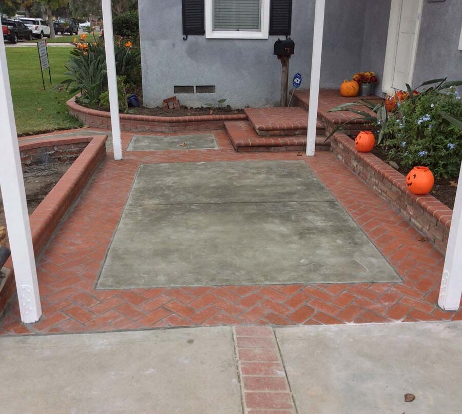New concrete slab with brick ribbon, brick planters, and front porch. Pacificland Constructors