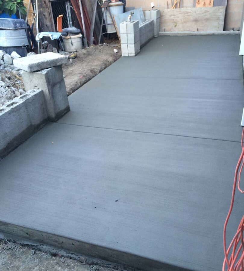 New broom swept concrete backyard patio. Pacificland Constructors