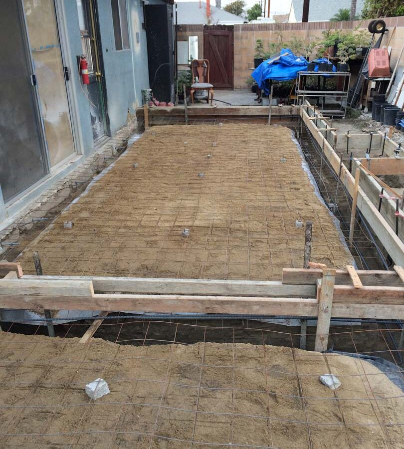 Wooden formwork and steel reinforcement for a new broom swept concrete backyard patio. Pacificland Constructors