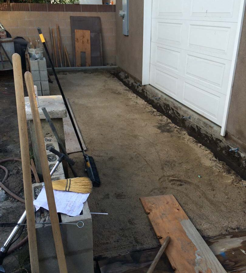 Grading and steel dowel into existing garage slab for a new broom swept concrete backyard patio. Pacificland Constructors