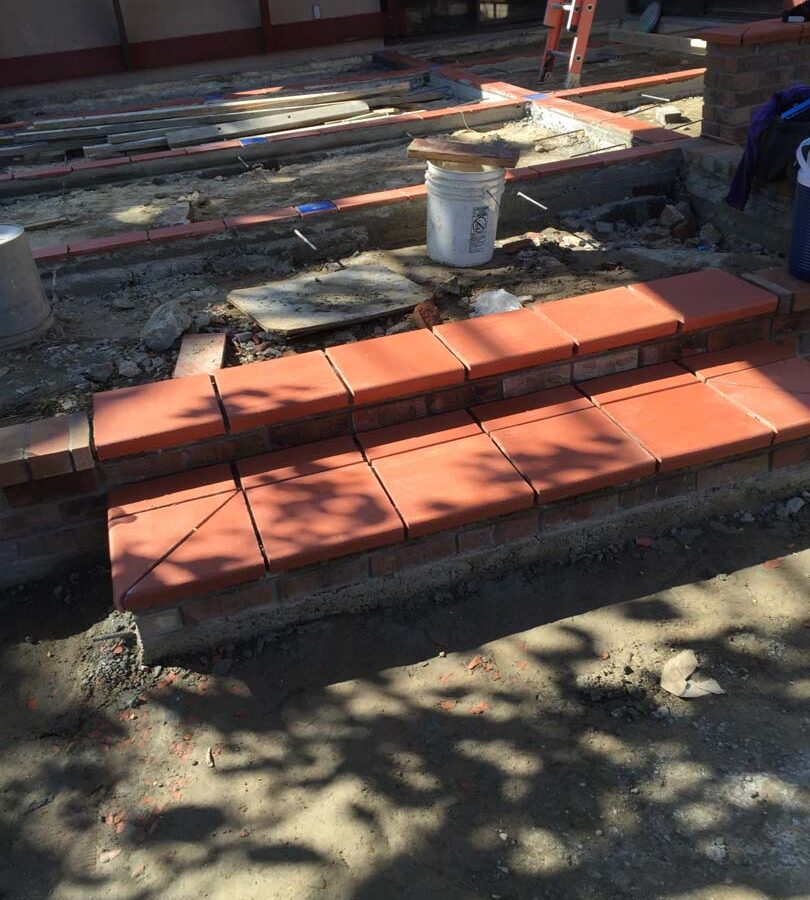Construction of bull-nosed steps for a new broom swept gray concrete patio with brick ribbons. Pacificland Constructors