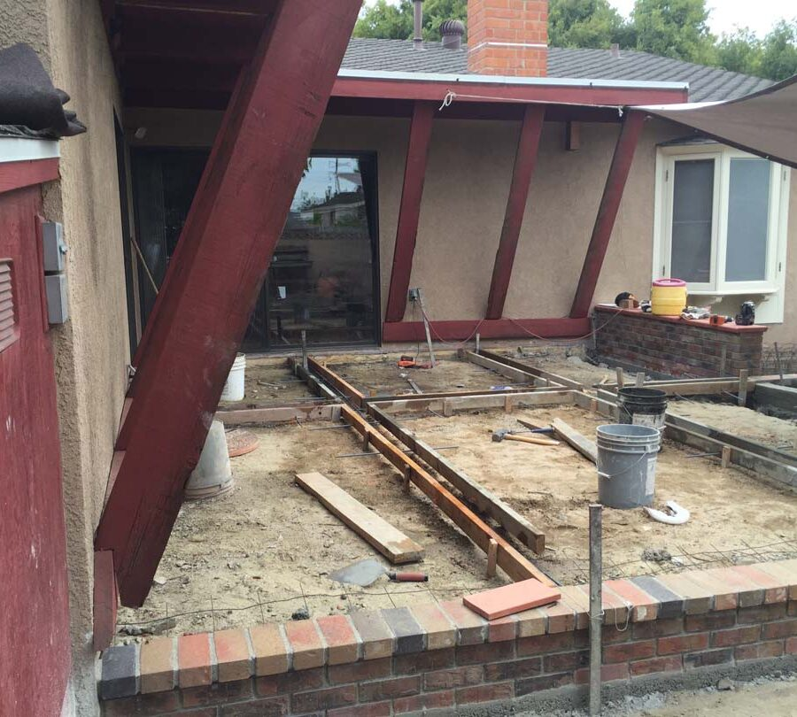 Construction of a new gray concrete patio with brick ribbons. Pacificland Constructors