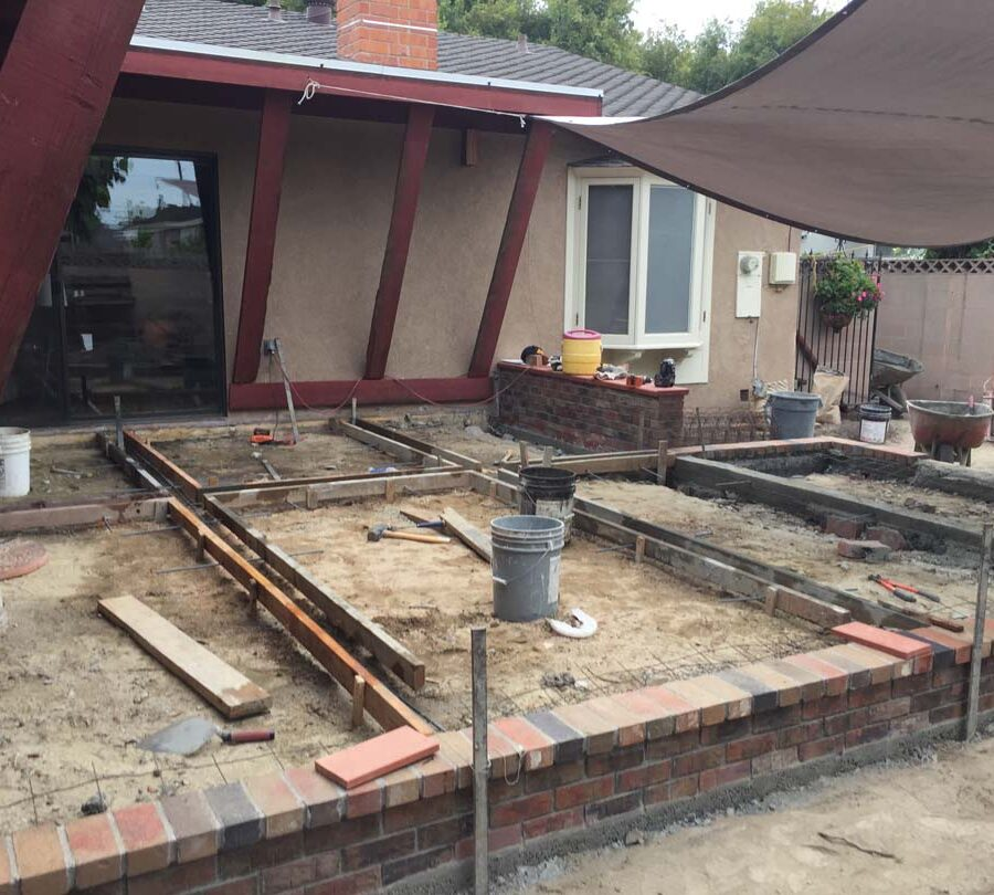 Construction of a new raised gray concrete patio with brick ribbons. Pacificland Constructors