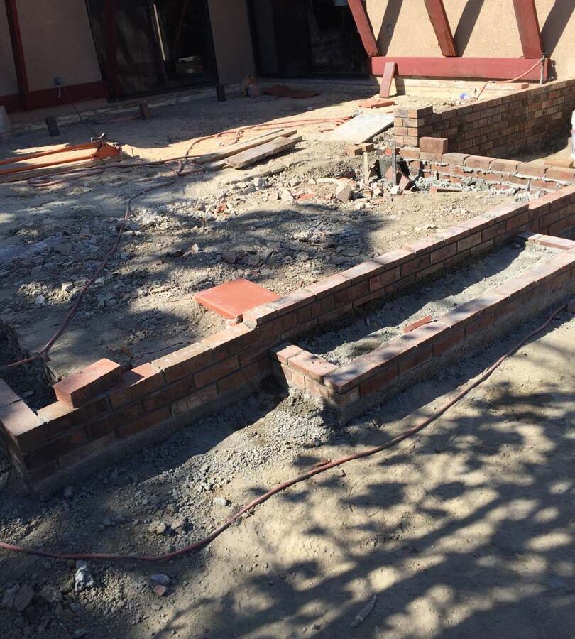 Construction of a new raised gray concrete patio with brick ribbons and brick steps. Pacificland Constructors