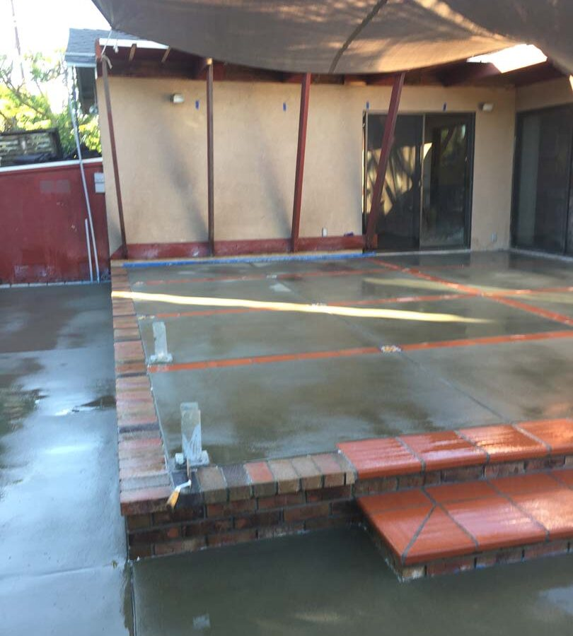 New broom swept gray concrete patio with brick ribbons and bull-nosed brick steps. Pacificland Constructors