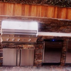 New custom bbq with stone veneer around the dishwasher, fridge, and BBQ grill. Topped off with a flagstone slate countertop.