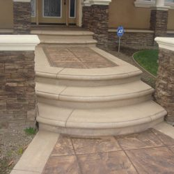 New custom entrance with stamped colored concrete, stone covered pilasters, and concrete precast bull-nosed edges.