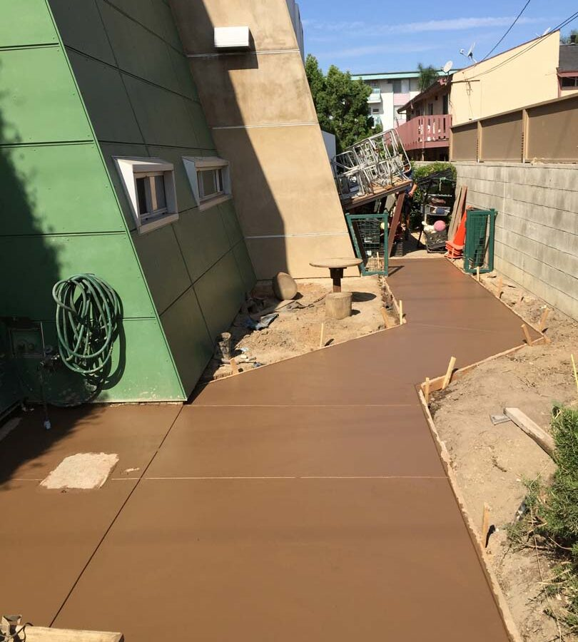 New backyard colored concrete walkway on the sides and backyard with hand scorched joints. Pacificland Constructors