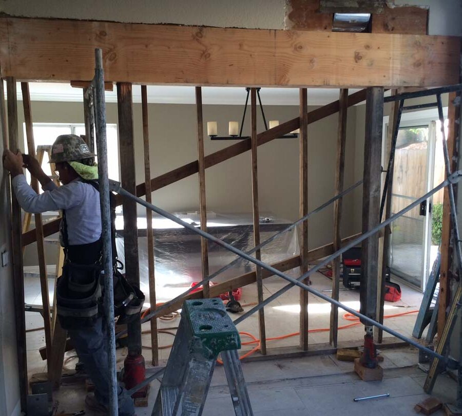 Lally columns are placed to reinforce the ceiling joists prior to removing the load bearing wall. Pacificland Constructors