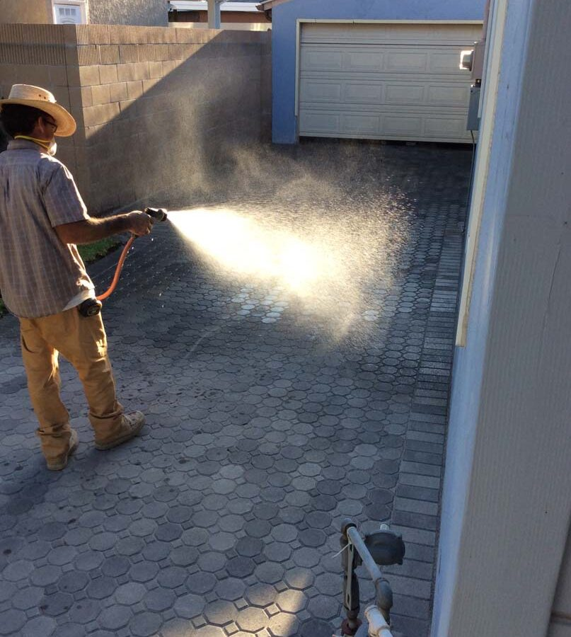 Martin, founder of Pacificland, wetting the applied silica sand so it settles between the joints of new concrete pavers for a home's new driveway. Pavers are a great option to raise the value of your home. Pacificland Constructors