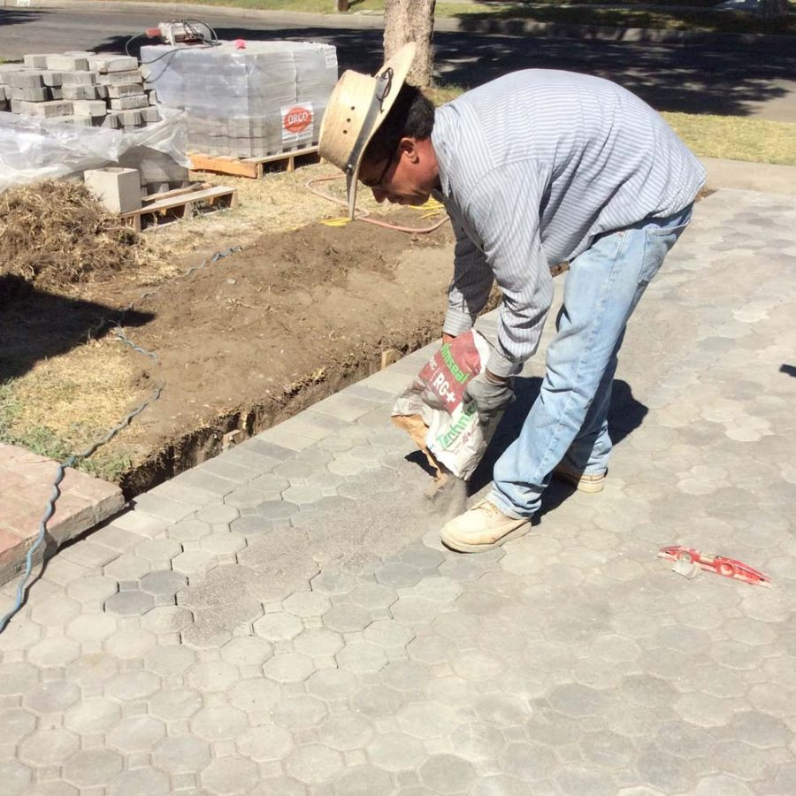 Martin, founder of Pacificland, applying silica sand between the joints of new concrete pavers for a home's front yard. Pavers are a great option to raise the value of your home. Pacificland Constructors