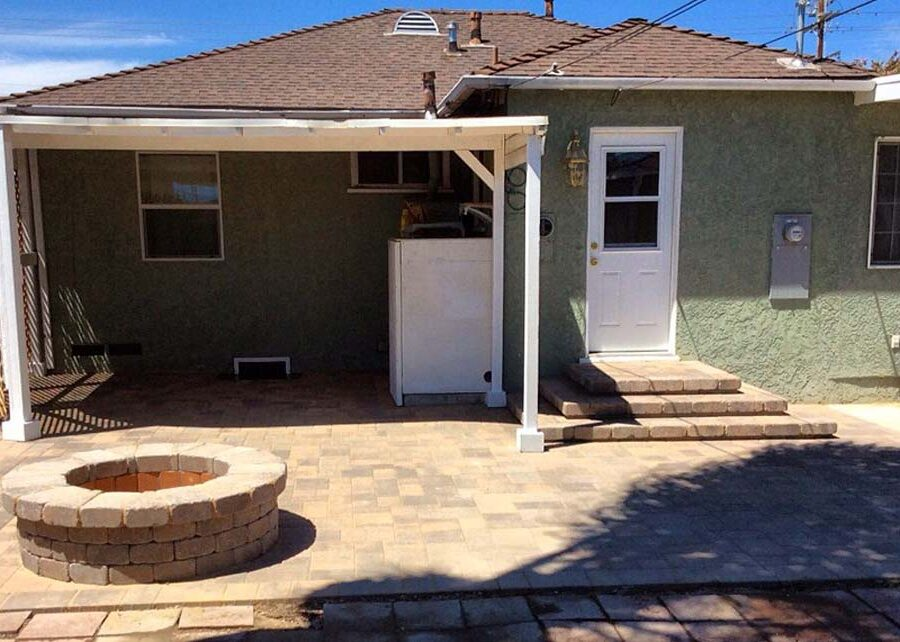 New backyard patio, steps, landing, and firepit built with colored concrete pavers for a residential project.