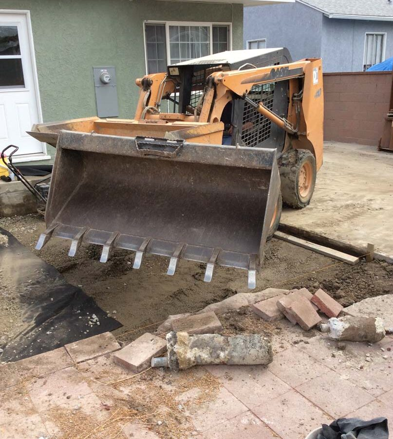 Construction equipment was used to remove the existing slap and grade the soil prior to setting up pavers.