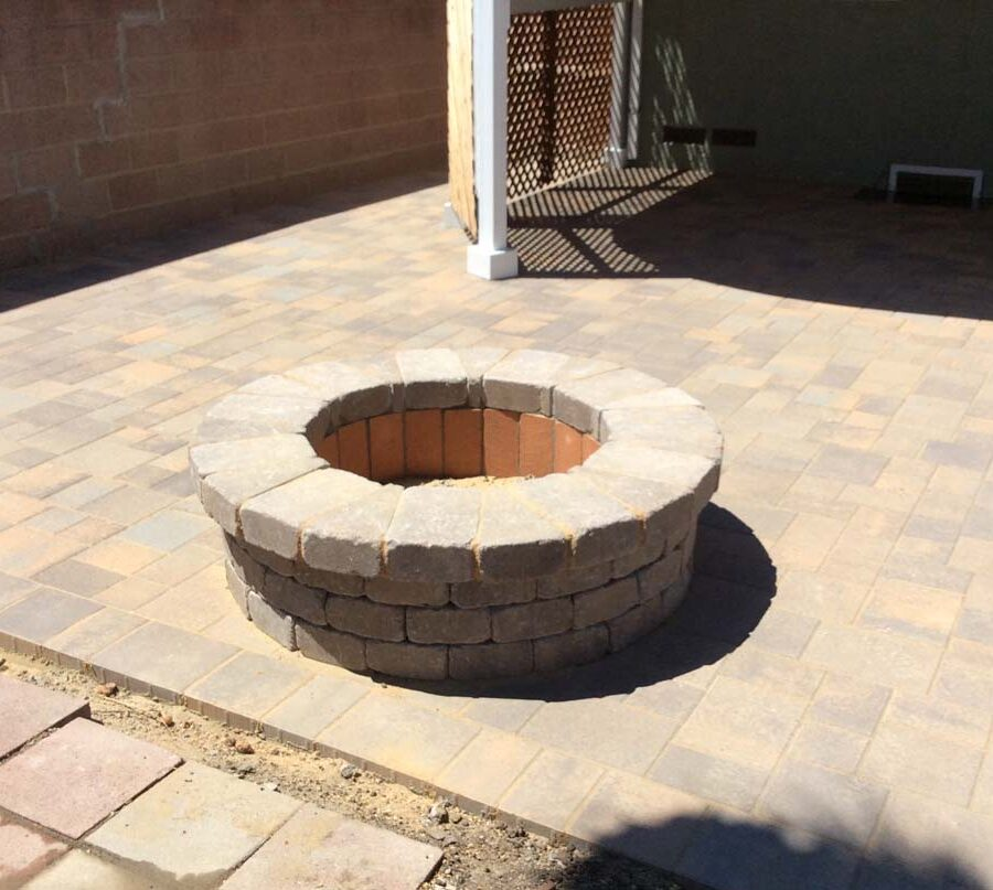 New backyard patio and firepit built with colored concrete pavers for a residential project.