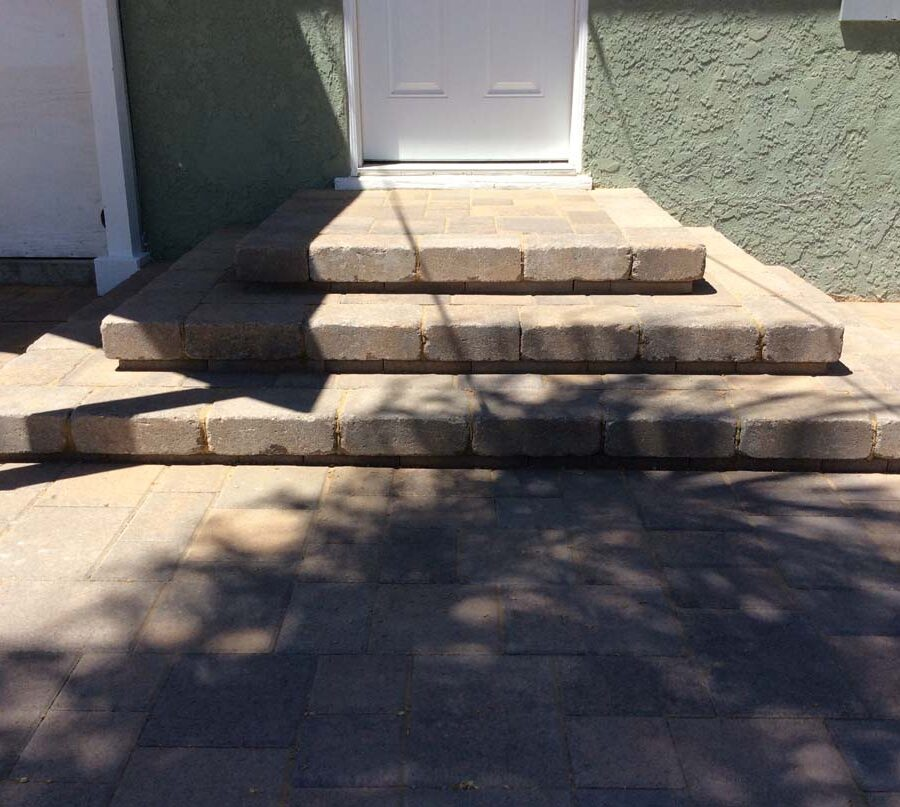 New backyard patio, steps, and landing built with colored concrete pavers for a residential project.