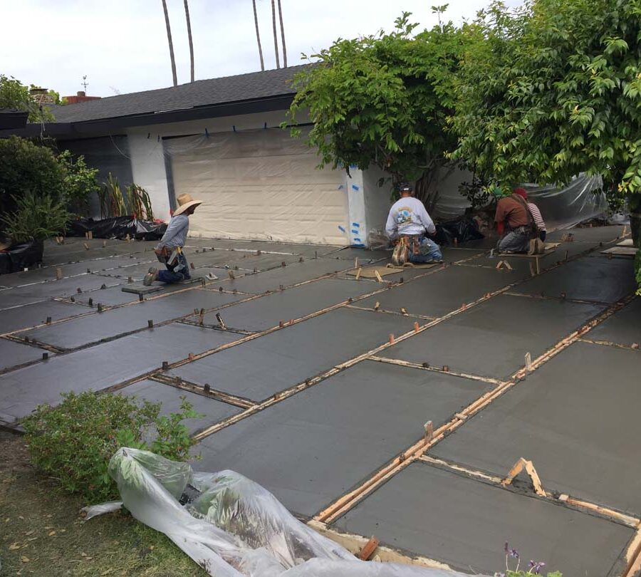 Concrete finishing a new front yard patio with gaps used to create an architecturally nature-friendly theme. Pacificland Constructors